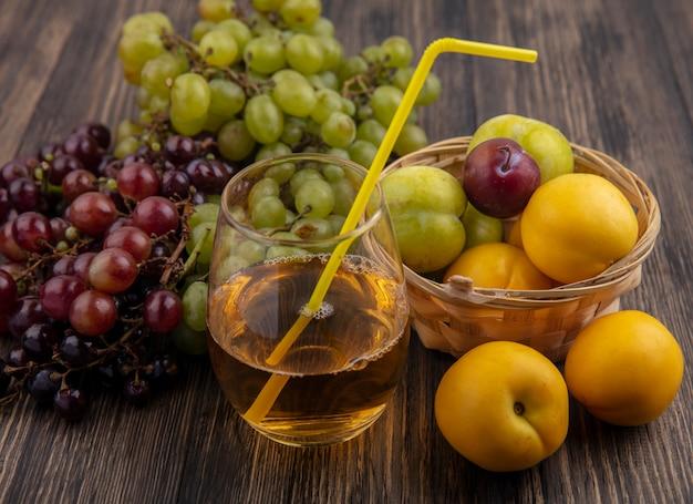 Vista laterale del succo d'uva bianca in vetro con frutta come nectacots pluots nel cesto con uva su fondo in legno