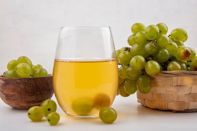 Vista laterale del succo d'uva bianca in vetro con uva bianca nella ciotola e nel cesto su sfondo bianco