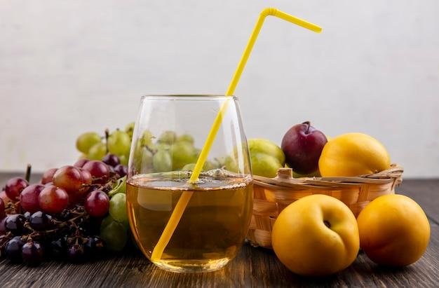 Vista laterale del succo d'uva bianca con tubo per bere in vetro e frutta come nectacots pluots nel cesto con uva su una superficie di legno e sfondo bianco