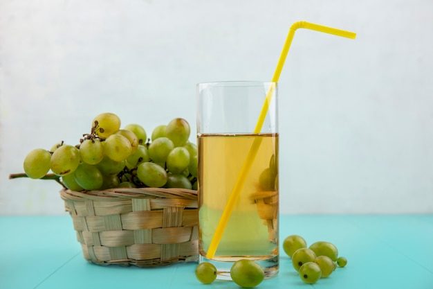 Side view of white grape juice with drinking tube in glass with white grape in basket and on blue surface and white background