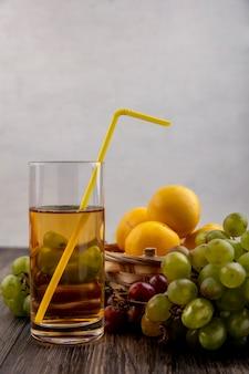 Vista laterale del succo d'uva bianca con frutti come nectacots nel carrello con uva su fondo in legno
