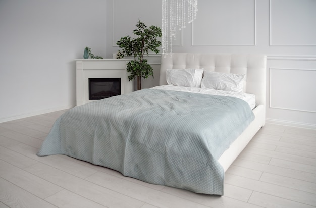 Side view of white leather bed with blue bedsheet and fireplace