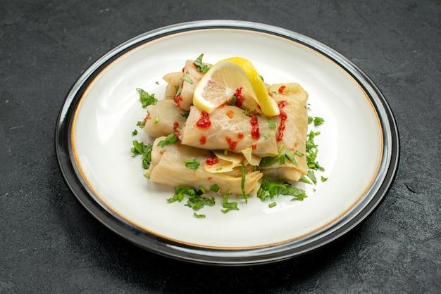 Вид сбоку белая тарелка пищевого блюда из голубцов с соусом из лимона и зеленью на белой тарелке на черном фоне