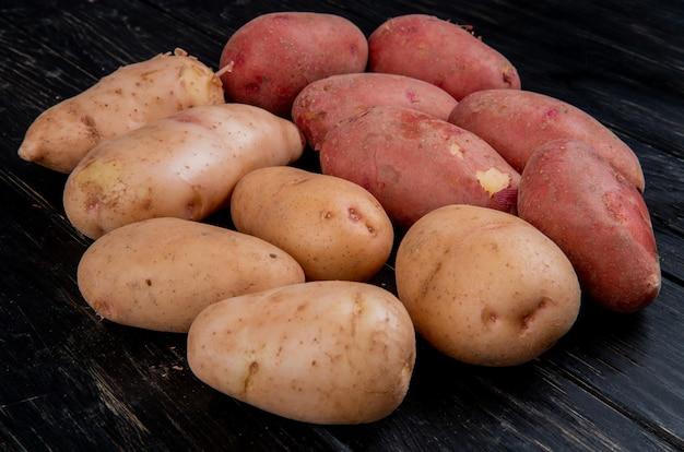 Vista laterale delle patate bianche e rosse sulla tavola di legno