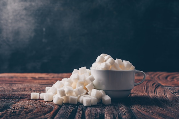 Side view white sugar cubes in a cup on dark and wooden table. horizontal