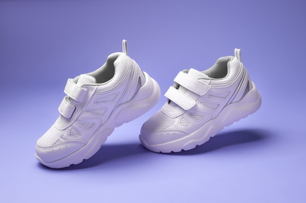 Side view white unisex sneakers with velcro fasteners hanging heels in the air isolated on a purple ...