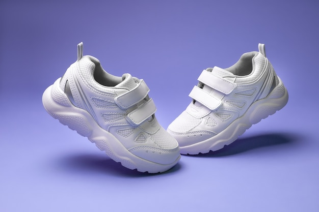 Side view white unisex sneakers with velcro fly in the air toes to each other isolated on purple bac...