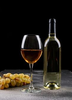 Vino bianco di vista laterale con l'uva sul verticale nero