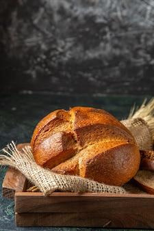 Vista laterale del pane nero fresco intero e tagliato in una scatola di legno marrone sulla superficie di colori scuri