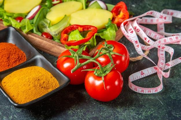 Vista laterale di verdure fresche tagliate intere e spezie metro su colori della miscela