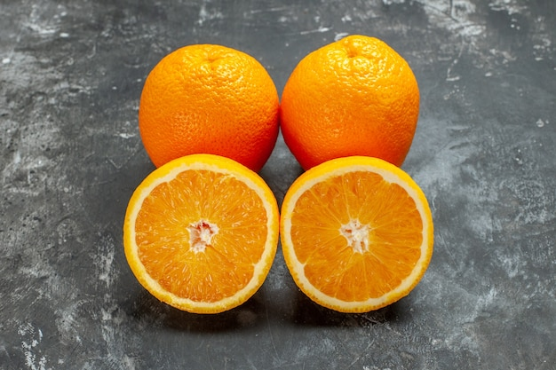 Side view of whole and cut natural organic fresh oranges lined up in two rows on dark background