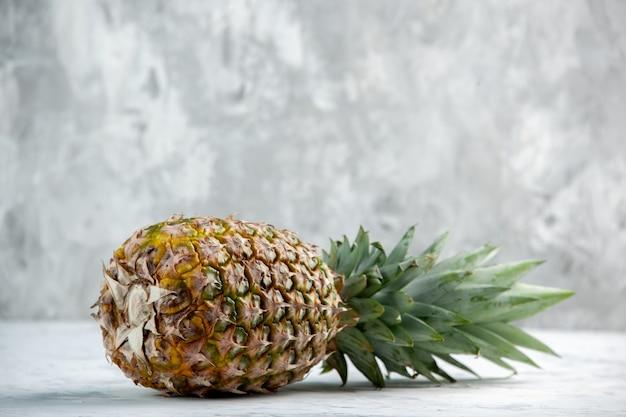 Vista laterale dell'intero ananas dorato che cade fresco sulla superficie di marmo