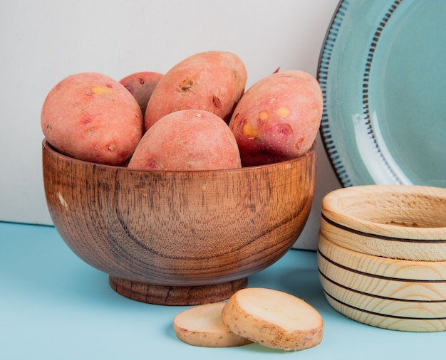Side view of whole potatoes in bowl with sliced ones and black pepper and plate on blue surface and white background