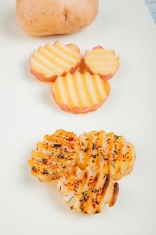 Vista laterale dell'intera patata affettata e fritta su superficie bianca