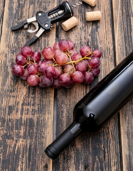 Side view wine bottle with grape on dark wooden vertical