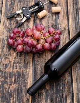 Bottiglia di vino di vista laterale con l'uva sul verticale di legno scuro