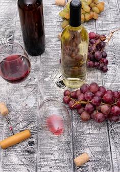 Bottiglie di vino di vista laterale con l'uva sul verticale di legno bianco
