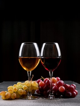 Side view wine glasses with grape on black vertical
