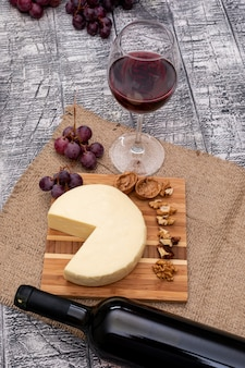 Side view wine with grape and cheese on board and on white wooden vertical