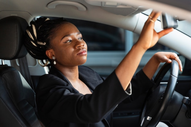 Side view of woman adjusting her car mirror