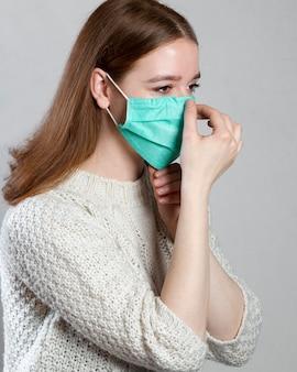 Vista laterale della donna che adegua la mascherina medica sul viso