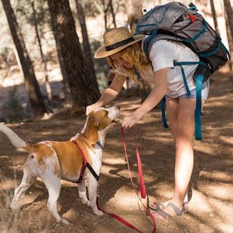 Вид сбоку женщина и ее собака, хорошо проводящие время