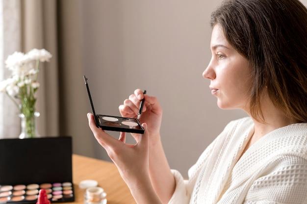 Side view woman applying eyeshadow