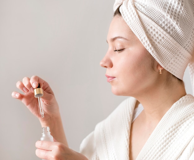 Side view woman applying face serum