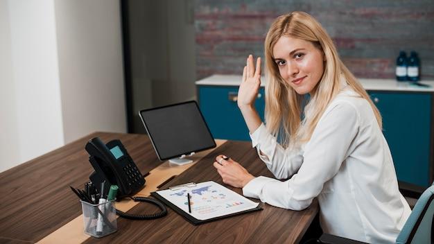 Вид сбоку женщина в офисе машет