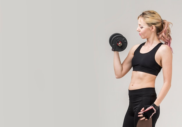 Side view of woman in athleisure lifting weight with copy space