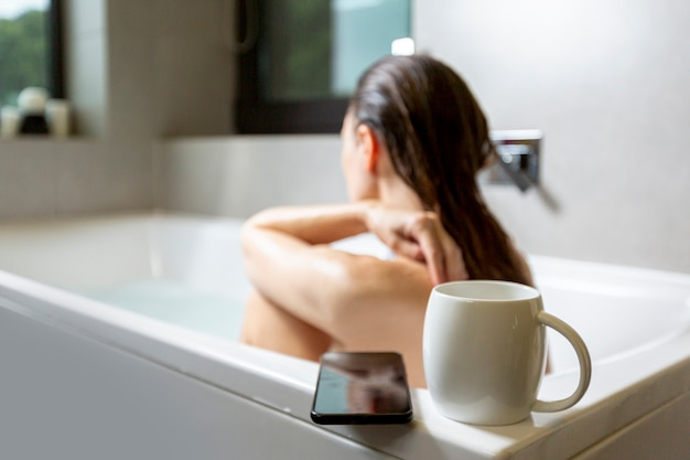 Side view woman in bathtub with coffee mug