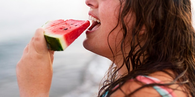 Side view of woman at the beach eating watermelon