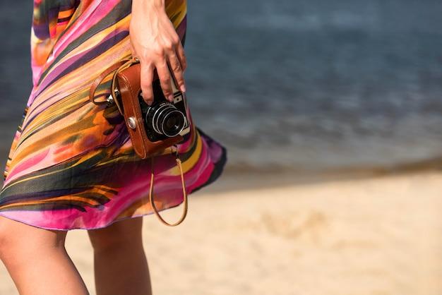 Vista laterale della donna in spiaggia tenendo la fotocamera