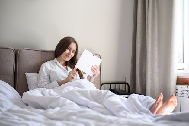 Side view of a woman in bed with a tablet