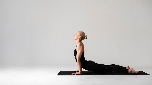 Side view woman in black clothes with yoga mat