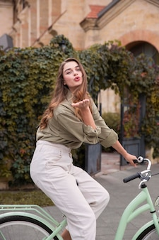 Side view of woman blowing kiss while riding bicycle outdoors