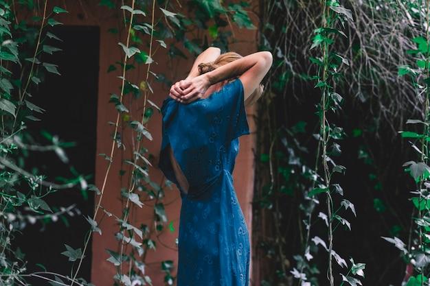 Боковой вид женщина застегивает платье возле старого дома