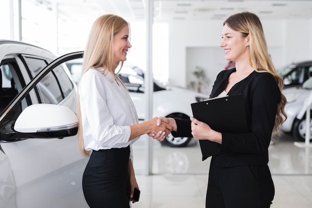 Side view of woman buying new car