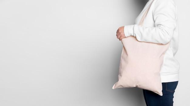 Donna di vista laterale che trasporta lo spazio della copia della borsa di tote del tessuto