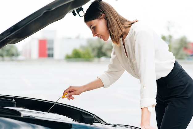 Side view of woman checking engine