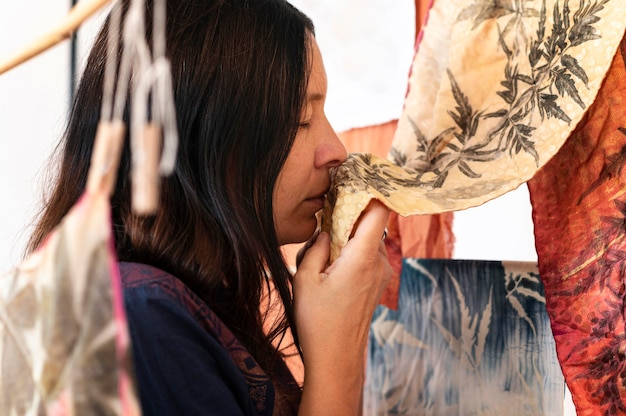 自然な着色された布をチェックする側面図の女性