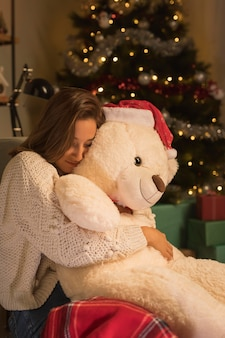 Side view of woman on christmas hugging her teddy bear with santa hat