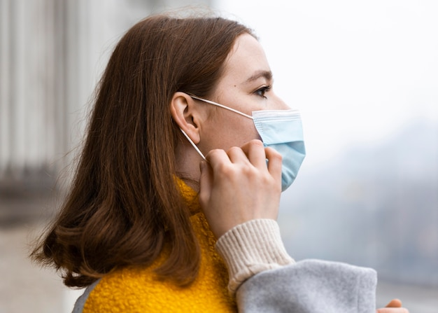 Side view of woman in the city adjusting her medical mask