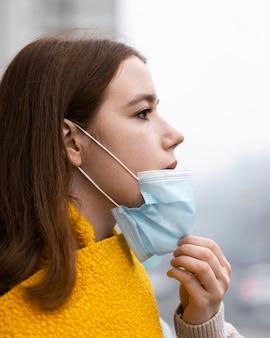 Vista laterale della donna in città rimuovendo la sua maschera medica