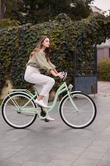 Side view of woman in the city riding a bicycle