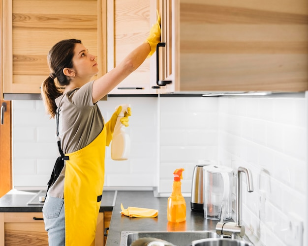 Side view woman cleaning cabinet