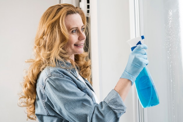 Side view of woman cleaning window