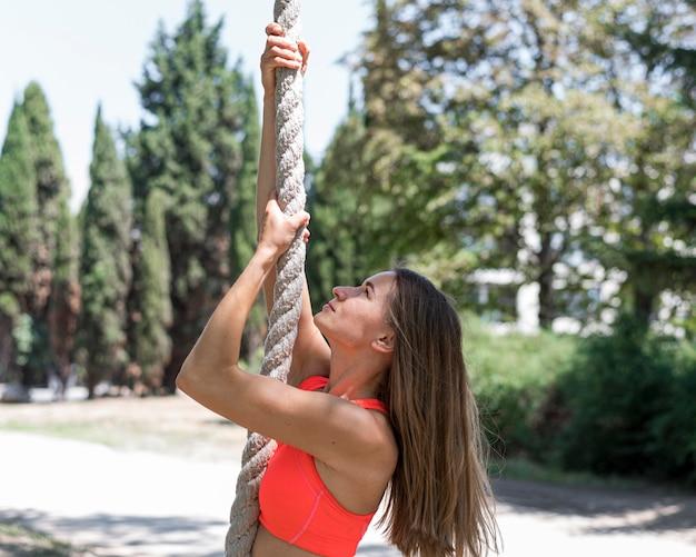 Вид сбоку женщина, поднимающаяся по веревке