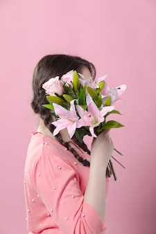 Side view of woman covering her head with bouquet of lilies