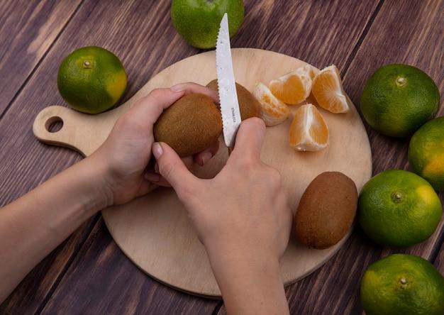 La donna di vista laterale taglia il kiwi su un tagliere con i mandarini verdi su una parete di legno